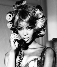 Naomi is on the phone while she waits for her hair to be curled using cans. Patrick Demarchelier.