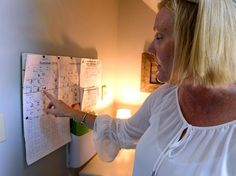 Scituate 07/09/2018: Lisa Blake, a professional organizer, looks at the schedule in the Command Central space of her Scituate home. The space was created to organize and post her three boys schedules for upcoming events. Photo by Debee Tlumacki for the Boston Globe (regional)