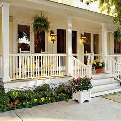 Hanging Ferns—Add charm with hanging ferns—a quintessential feature for any Southern porch. Cheery containers also add inviting color to this porch. | SouthernLiving.com