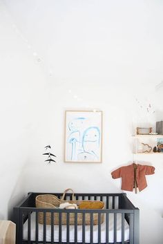 a cute minimal, gender neutral nursery! with a lovely mobile, wall art and moses basket