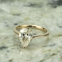 Edwardian Inspired Pear Shape diamond engagement ring. A lovely 1.67 ct pear shaped diamond that has been certified by the GIA as K color and SI1 clarity (report #2175355968) is set in an elegant tulip-styled solitaire engagement ring. 18k rose gold. The ring is a size 6 and may be resized, please inquire.