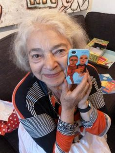 Artist Mirka Mora with the iPhone cover of her art.