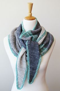 Migee is an asymmetrical scarf/wrap. Wide in the middle to provide warmth with elongated tapered ends to create the perfect shape for wrapping around your neck and casually knotting or draping.  Knit flat, from side to side in garter st, Migee features contrasting eyelet stripes in the body and a matching eyelet border, which is picked up and knit in the round after completing the main section.  Choose a gradient yarn and complementary contrast color or go with your favorite contrasting…