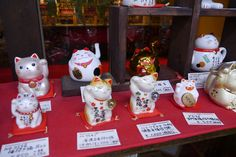 The maneki-neko (beckoning cat) is a common Japanese figurine (lucky charm, talisman) which is often believed to bring good luck to the owner. The figurine depicts a cat (traditionally a calico Japanese Bobtail) beckoning with an upright paw, and is usually displayed—often at the entrance—of shops, restaurants, pachinko parlors, and other businesses.