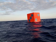 Aqua Dice - they are considered one of the most compelling symbols of dumb luck, and american artist max mulhern decided to explore this with his project 'aqua dice' -  the 'greatest floating craps game on earth'. two large, brightly colored die have been launched in international waters to create a visual ode to chance and good luck.