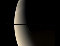 "This is a still from the video of a crescent Rhea transiting a crescent Saturn. You have to look carefully to the night side of Saturn (on the right) to see Rhea's faint crescent just below the rings. The photo is edge-on to the rings which show up as a dark line. Mona Evans, ""Rhea Moon of Saturn"" http://www.bellaonline.com/articles/art56119.asp"
