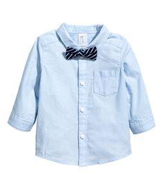 Vaaleansininen. Pitkähihainen paita pehmeää pintaraitaista puuvillakangasta. Yksi rintatasku, napit edessä ja kevyesti pyöristetty helma. Mukana