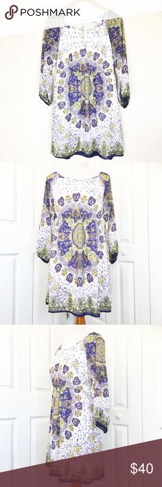 """Entro Boho Dress Cute little dress made by Entro.  All white dress with an all over Paisley/floral print in beautiful colors of purple and yellow.  Features a scoop neckline with key hole opening in the front and back.  Buttons at nape of neck with a mother of pearl button.  Material is made of 100% polyester.  Measurements laid flat: bust 18"""", waist unstretched 16"""", hip 22"""", and length from top of shoulder to hem 33"""".  Dress is fully lined. Entro Dresses"""
