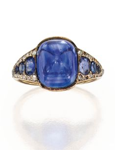 Gold, sapphire and diamond ring. Centered by a sugarloaf cabochon sapphire weighing approximately 8.50 carats, flanked by six cushion-cut sapphires weighing approximately 1.00 carat, further accented by 38 rose-cut diamonds, size 5, five diamonds missing; circa 1900.  E