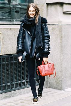 A thick-knit scarf is paired with a leather shearling-lined moto jacket, skinny jeans, sneakers, and a red Céline mini tote bag