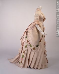 Dress, ca. 1882, silk and cotton with metal. This intricately cut evening dress is made of pale pink silk faille embellished with a silk-embroidered border of multicolored running floral motifs.