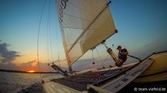 sailing straight forward into the sundown at lake cospuden, near leipzig, on a topcat k3 catamaran.  direkt in den sonneuntergang segeln, mit einem topcat k3, auf dem cospudener see bei leipzig.  segler: marcus viefeld foto: gopro hero 3 hd