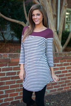 """This navy and wine striped top has such a long, flattering fit! In a color combination that is all fall, all day, there's no legitimate reason to turn this adorable top down!   Bra-friendly! Material has fair amount of stretch.  Miranda is wearing the small.   Length from shoulder to hem: S- 32""""; M- 33""""; L- 34""""."""