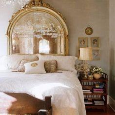 gilded mirror as headboard + soft and feminine bedroom