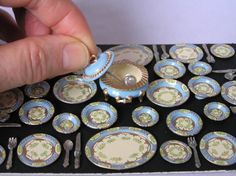 A hand-painted six-setting miniature dinner service in one twelfth scale. Painted by myself on British made metal miniatures. Six settings each comprising of a dinner plate, side plate, soup bowl, dessert bowl and cutlery. Also included are two oval serving platters, two round vegetable dishes, and a lidded soup tureen with ladle. A pale blue colour with gold and floral decoration on cream panels. The dinner plates measure 2cm in diameter and the side plates are 1.5cm in diameter. This is a…