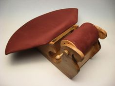 "Red ""sleigh"" roller pillow. The apron lifts up and there's a storage compartment underneath."