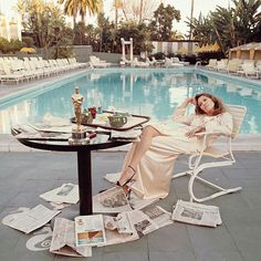 """""""Oscar Ennui"""" • American actress Faye Dunaway takes breakfast by the pool with the day's newspapers at the Beverley Hills Hotel, 29th March 1977. She seems less than elated with her success at the previous night's Academy Awards ceremony, where she won the 1976 Oscar • Terry O'Neill"""