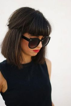 Model sports a shoulder-length hair with fringe and signature glasses