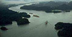 Navio cargueiro segue em direção ao oceano Pacífico por meio de um lago artificial rodeado por florestas tropicais, formando uma parte substancial do canal do Panamá, no lago Gatún
