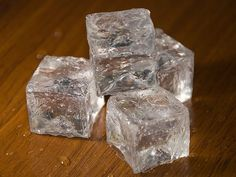 Fake Ice - Make a square foil mold using a small block of wood.  Fill with plastic jewelry beads and cook in the oven for about 20 minutes at 375 degrees.  Monitor as the cubes bake. If the melting beads get lower than you want, throw some more in. Once melted pull from the oven and let cool. Depending on how well you made your mold, you might have to file some edges down.  And there you have it, fake ice...