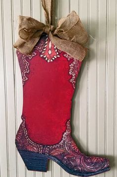 This colorful wood cowboy boot wall hanging is sure to add western style to your home. The center has room for personalisation if you like and the burlap bow hanger makes it adorable. This would be ni