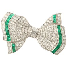 Art Deco Elegant Calibre Cut Emerald Diamond Platinum Bow Brooch | See more rare vintage Brooches at https://www.1stdibs.com/jewelry/brooches/brooches