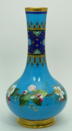 A Minton English porcelain Japonisme vase depicting flowers over light blue ground. Gold painted rim and foot.