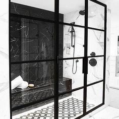 A black marble wall matched a black marble shower bench fixed against black and white mosaic floor tiles, as a matte black shower kit contrasts white and gray marble wall tiles. Black Tile Bathrooms, Black Marble Bathroom, Gray Marble, Master Bathrooms, Marble Top, Modern Bathroom, Bathroom Ideas, Master Bedroom, Window In Shower