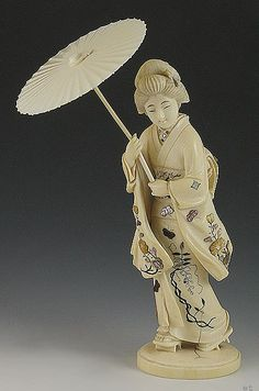Japanese carved ivory geisha figurine with spectacular shibayama inlay. The kimono is inlaid with exquisite mother of pearl, abalone shell, and lacquer or tortoise shibayama decoration in the form of beautiful flowers, leaves, and butterflies. The shibayama inlay is accented with black and green ink. This piece was made around the turn of the century