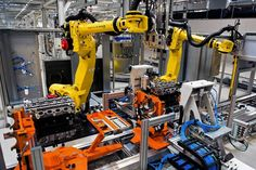 Automobile engines pass beneath Fanuc robots on the production line inside an Opel assembly plant...