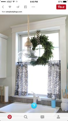 cute cafe rod...ring clipped curtains for bottom half, wreath above by way of white tension rod. Install removable shelf at halfway point. Use antique white farm light/remount over sink.