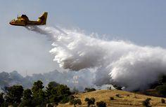 Warga setempat menyaksikan pesawat tempur menyirami kebakaran dengan air dekat rumah-tumah liburan di desa Costa, kawasan Argolida, di Yunani tenggara ketika kebakaran hutan berlangsung.