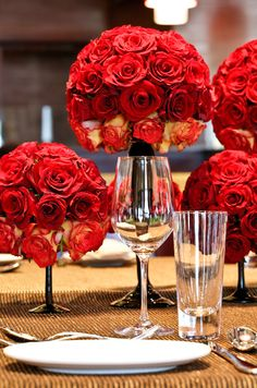 Pomanders of colorful red roses sit atop thin metallic vases for this chic dinner party.
