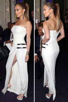 Jennifer Lopez at 2014 Paris Fashion Week arrived at the Versace Studio Show in the French Capital wearing a stunning, yet rather unusual white gown.  The strapless garment featured a thigh-high split as well as a sequined trouser leg and silver buckles.  She accessorised her look with two silver cuffs and matching statement earrings, and wore her hair up in a slicked back ponytail as she pouted for photographers.