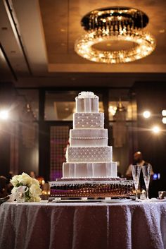 Five tiered square wedding cake with ribbon on top on silver cake stand and silver sequin linen - Photo by Jenny & Eddie