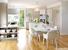 Warm, modern kitchen by Karin H Edwards with discreet work areas and a focus on dining/gathering. See HouseBeautiful.com