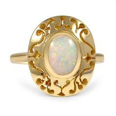 This Retro-era ring features a yellow gold setting showcasing an oval-shaped opal cabochon center stone framed by intricate pierced details. The soft swirling patterns surrounding the center stone assist in creating a distinctive appeal for this piece.