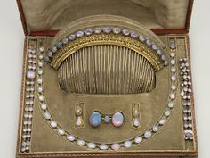 A complete gold and opal parure, consisting of a tiara comb, necklace, two bracelets, earrings and a brooch.