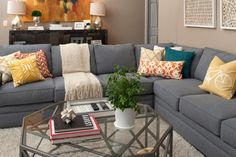 It's easy to picture this living room as a family's primary gathering space. The large sofa is durable yet attractive, and throw pillows and blankets in multiple patterns add to the sense of casual comfort. Because the room and sofa are neutral, it's simple to execute a design change when the homeowners desire — just switch out art and pillows for a fresh, new look.