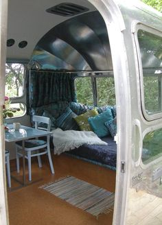 Peek inside a vintage Airstream camper trailer with cozy dinette and plush bench window seat Airstream Basecamp, Airstream Sport, Airstream Bambi, Airstream Vintage, Airstream Caravans, Vintage Camper Interior, Airstream Living, Airstream Remodel, Airstream Renovation