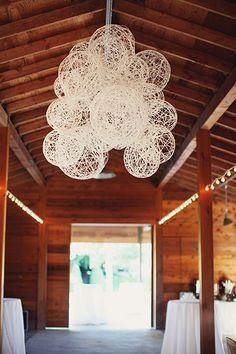 The space up above needs décor just as much as the space below! Adorn your ceiling fabric, lights, greenery, or these whimsical papier-mache yarn globes. It's a great trick to covering up any unsightly beams or tent poles.Related: Gorgeous Ideas for a Barn Wedding