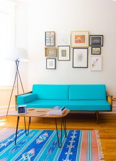 Kilim #rug matches this turquoise #sofa and helps extend the #gallery wall art to the entire room