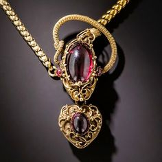 Victorian-era Necklace, serpent, crowned with a glowing cabochon garnet, graciously offering up a garnet-set heart locket, ca 1860.