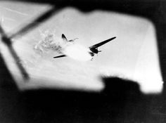 """An Imperial Japanese Navy Mitsubishi G4M (""""Betty"""") bomber is burning as it is shot down by a U.S. Navy Fleet Air Wing 2 (FAW-2) Consolidated PB2Y-3 Coronado patrol bomber in the Central Pacific. The Japanese plane wears the number """"72"""" on its tail fin. The photograph was released on 22 May 1944."""