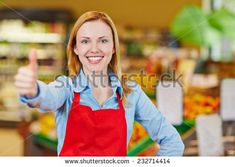 Young happy saleswoman in supermarket holding her thumbs up