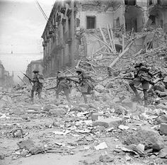 British troops scramble over rubble in a devastated street in Catania, 5 August 1943