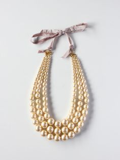"Pearl Triple Strand Statement Necklace: This stunning statement necklace features a triple strand of graduated glass pearls.The necklace is 15"" in length and is finished with an 18-karat gold plated brass and velvet ribbon closure."