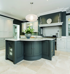 This bespoke kitchen by Tom Howley features a show-stopping island with real curve appeal, and classic cabinetry painted in a shade of slate grey. See more on the Beautiful Kitchens blog, kitchensourcebook.co.uk