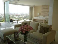 Diseño de dormitorio con uso de paleta de color en neutros con acentos de color en palo rosa.