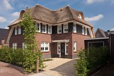 Classic 30's house with red brick and thatch in Tabaksteeg Leusden